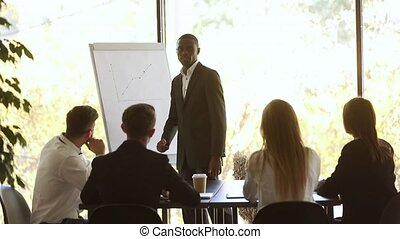 African coach stands near flip chart showing sales growth shown on raising graphic during corporate training, finish presentation with positive forecast and participants applauses express gratitude.
