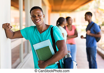african college boy with books standing by passage -...