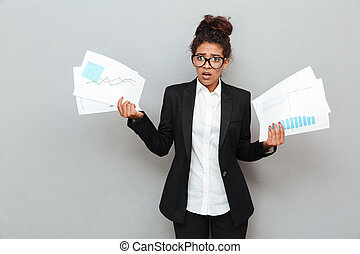 African confused business woman with diagramas documents