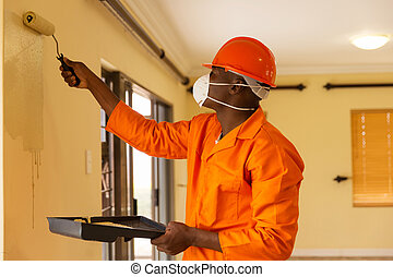 african construction worker painting the wall - professional...