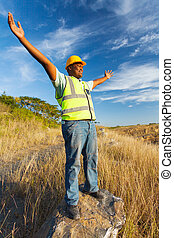 african construction worker with arms outstretched