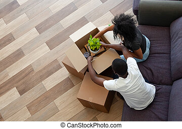 African couple packing boxes preparing for relocation, top view