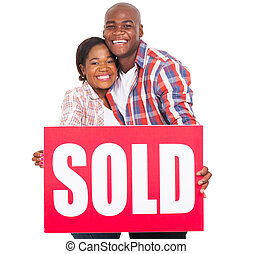 african couple showing sold sign