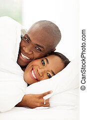 african couple sleeping in bed