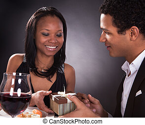 African Couple With A Gift In Hands - Portrait Of Young...