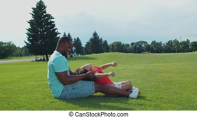 African dad and little son having fun outdoors