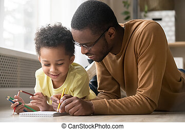 African dad and little toddler son draw with colored pencils