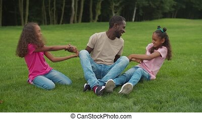 African dad with girls enjoying leisure outdoors - Two ...