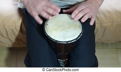 African Djembe drummer at home