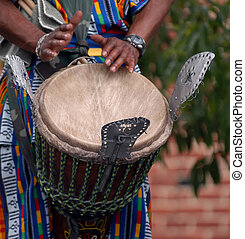 african drummer performs, this is a detail of hands beating the drum.