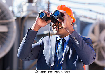 african electrician engineer using binoculars