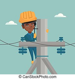 African electrician working on electric power pole - Young...
