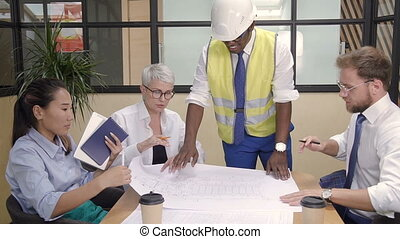 African engineer showing house blueprint to architects.