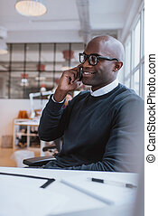 African executive using cell phone while at office