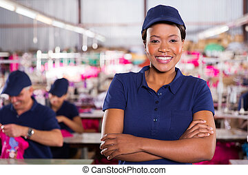 african factory worker with arms crossed