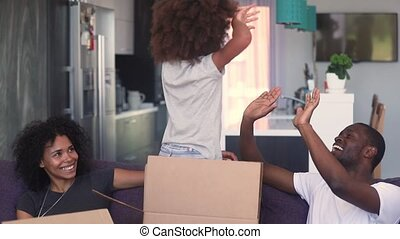 African family play with daughter celebrating moving at new house