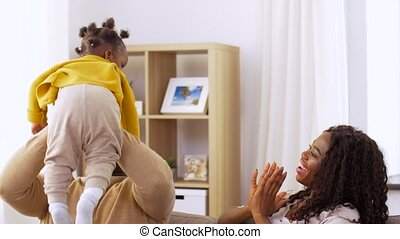 african family playing with baby daughter at home
