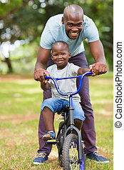 african father helping son ride a bike