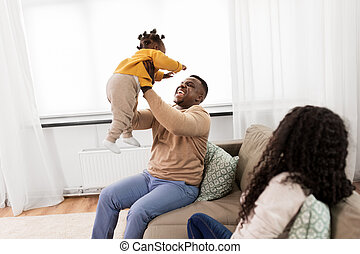 african father playing with baby daughter at home