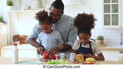 African father teaching son daughter cutting vegetable salad in kitchen