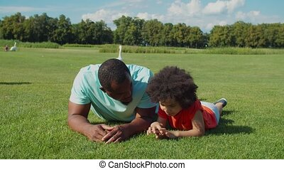 Positive affectionate attractive african american father with adorable little mixed race son with curly hair lying on green lawn, communicating and sharing while spending leisure in summer nature.