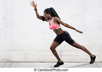 African female athlete in running position.