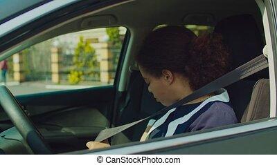 African female driver fastening seat belt in car