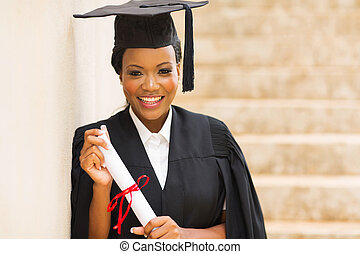 african female graduate standing outdoors