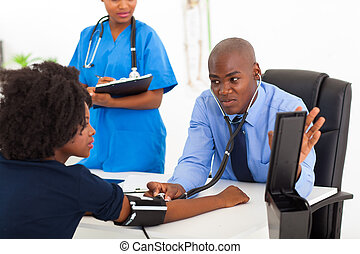 african general practitioner checking patient's blood...