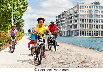 African girl cycling with friends along a river - African...