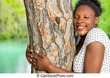 African girl embracing tree in woods.
