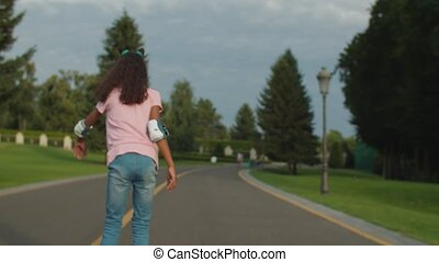 African girl learning to ride roller skates in park - Rear ...