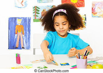 Cute African girl playing developmental game putting cards matching relations on table while sitting in playroom with wall behind full of children drawings