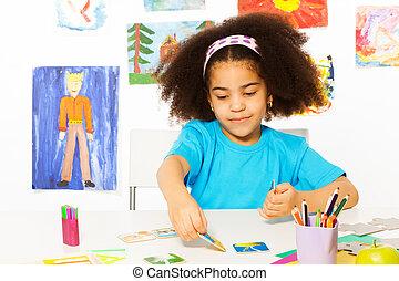African girl plays developmental game putting card