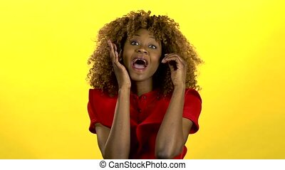 African girl rejoices in the win. Yellow background. Slow motion
