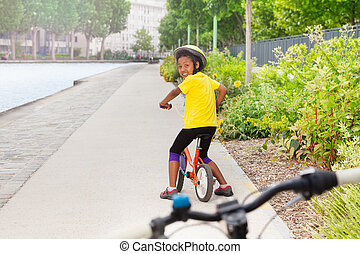 African girl riding bicycle on cycle lane in city