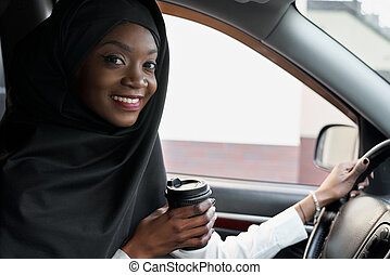 African girl sitting in car, holding coffe cup.