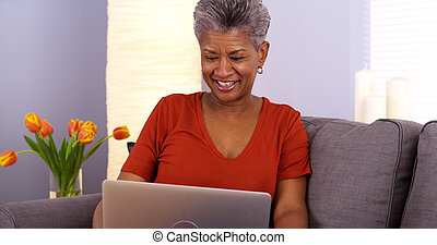 African grandmother laughing and talking on laptop