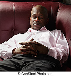 African guy having nap on red leather sofa