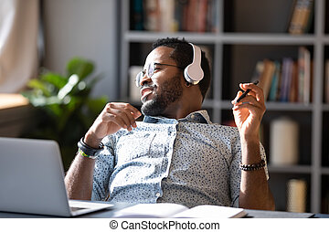 African guy wear headphones listening music enjoy break at workplace