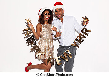 African happy young loving couple holding happy new year garland.