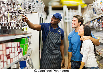 african hardware store assistant helping customers -...