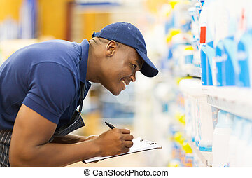 african hardware store worker taking stock - cheerful...