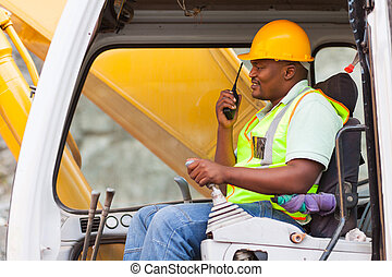 african industrial worker operating bulldozer while talking...