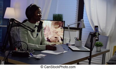 African influencer wearing headphones checking sound recording new podcast series at home studio for channel. On-air online production internet broadcast show host streaming live content