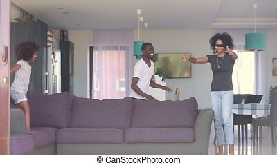 Happy african ethnicity family play hide and seek game in living room at home, blindfolded mother try to catch daughter and husband, parents little kid having fun laughing spending free time together
