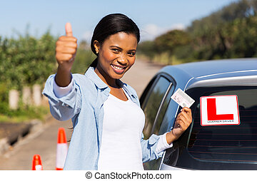 african learner driver holding her driver's license -...