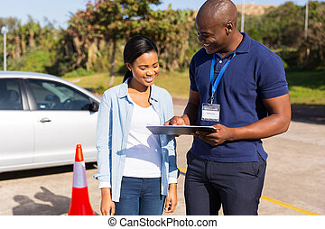 african learner driver with instructor before talking...