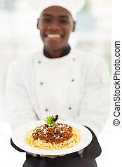 african male chef presenting spaghetti
