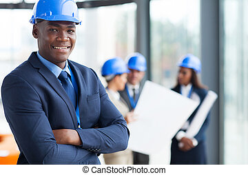 african male construction manager with arms folded